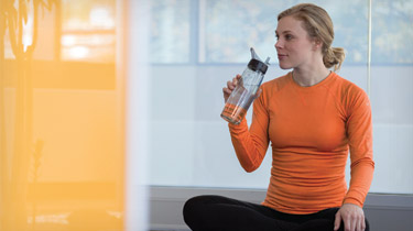 Woman in workout clothes sitting on the floor drinking water from a water bottle