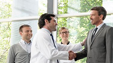 Doctor shaking the hand of man in suit white two others watch